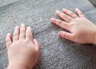 Italia Felix mani di un bambino su testo braille